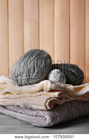 Warm clothes and cotton on wooden wall background