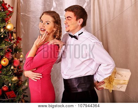 Couple on party recieve gift near Christmas tree. Vintage style.