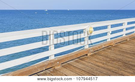 Wooden Pier With Blue Ocean And Sky Background.