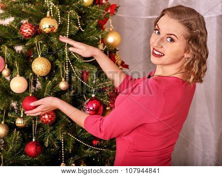 Beautiful woman dressing Christmas tree. Vintage style.