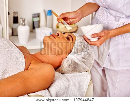 Woman middle-aged in spa salon receiving facial mask by  beautician.