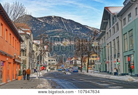 GARMISCH-PARTENKIRCHEN GERMANY - JANUARY 06 2015: Small Alpine town street with typical houses people walking down the street mountains in the background. Garmisch-Partenkirchen Bavaria Germany
