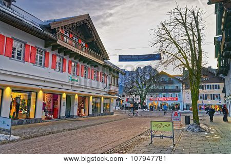 GARMISCH-PARTENKIRCHEN GERMANY - JANUARY 06 2015: Cozy street of Garmisch-Partenkirchen with colorful houses and stores decorated for Christmas holidays