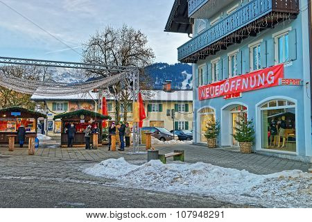 GARMISCH-PARTENKIRCHEN GERMANY - JANUARY 06 2015: Square in Garmisch-Partenkirchen with houses decorated for the winter holidays and unidentified people eating traditional Christmas food