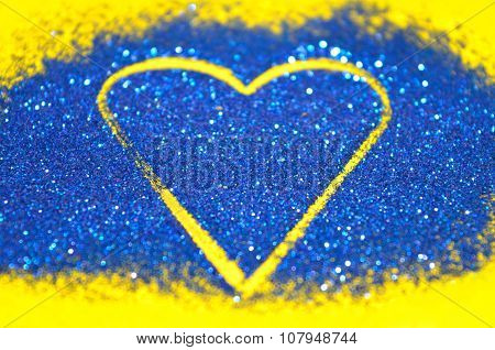 Blurry abstract background with heart of blue glitter sparkle on yellow surface