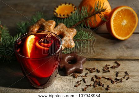 Mulled wine with spices and biscuits on wooden background