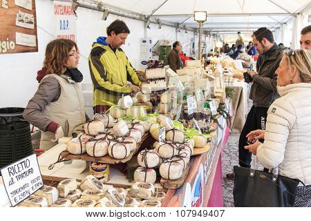Moncalvo, Italy - October 18,2015: Tourists In Front Of A Cheese Vendor At The Truffle Fair Of Monca