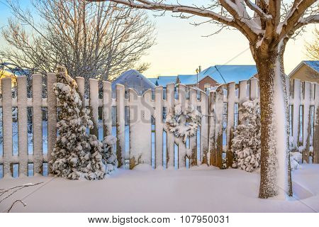 A garden gate decorated with a Christmas wreath all covered in snow.