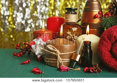 Composition of alight candles, towel and aroma oil on green wooden table against sparkle background