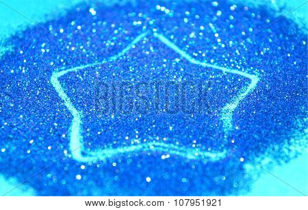 Blurry abstract background with star of blue glitter sparkles on blue surface
