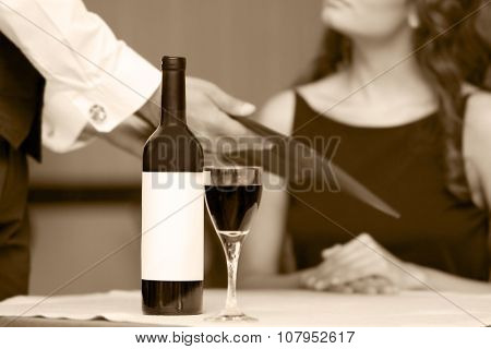 Portrait of beautiful woman with wine card at restaurant, black and white retro stylization