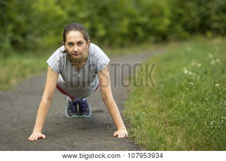 Young girl doing push ups from the ground in training outdoors.