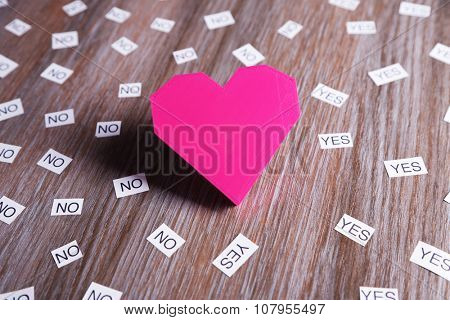 Pink heart with yes and no on wooden background