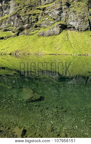 Reflections of grassy hill and rock face in a calm mountain lake