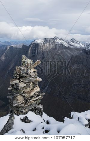 The cairn atop the mountain Kongen (the King) in Norway. The Troll peaks towers in the background.