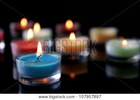 Colourful alight candles in a row on black background, blurred