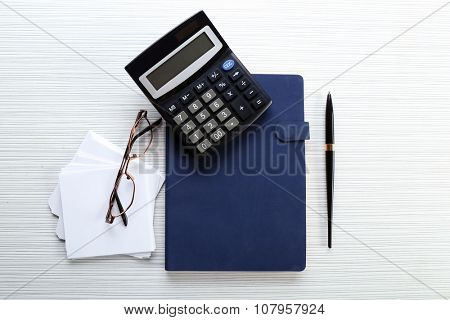 Blue notebook with stationery on white paper background