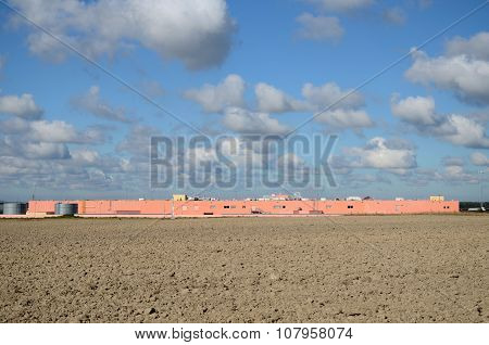 Storehouse on the background field and sky with clouds