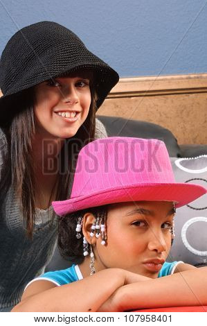 cute African American girl and Caucasian girl friend with hats on their heads having fun with them