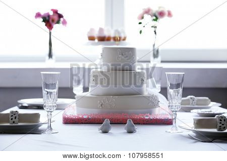 Layered wedding cake on decorated table in restaurant