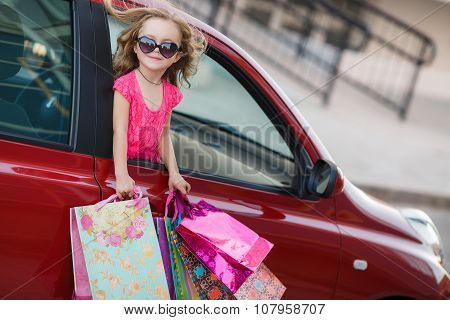 Happy child in the car with colored bags