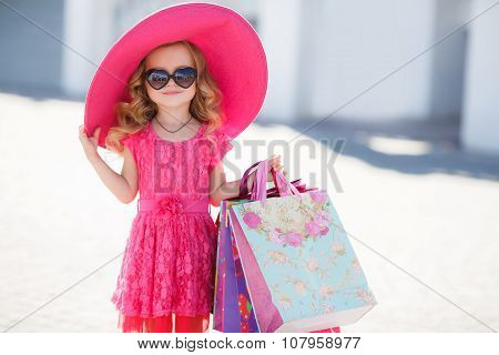 Fashionable little girl in a hat with shopping bags