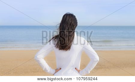 Woman watching the sea, her hands on her hips, seen from the back