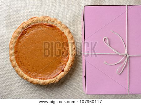 High angle shot of a holiday pumpkin pie and pink bakery box. Horizontal format.