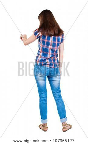 back view of young woman presses down on something. Isolated over white background. Rear view people collection. A young girl in a checkered blue with red stripes presses index finger.