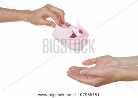 Concept of childish goods sale -one woman hand gives baby bootees to another, isolated on white background