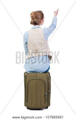 back view of woman  in vest sits on a suitcase and pointing. beautiful  girl in motion.  backside view of person.  Rear view people collection. Isolated over white background.