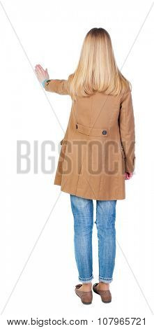 back view of woman in brown cloak. Young woman presses down on something. Isolated over white background. Rear view people collection. backside view of person. she holds his hand open, palm forward