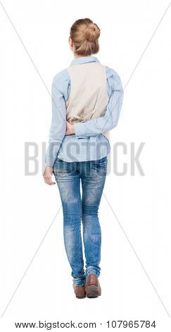 back view of standing young beautiful  blonde woman in brown vest. girl  watching. Rear view people collection.  backside view of person.  Isolated over white background.