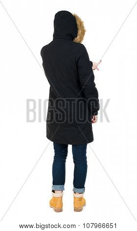 Back view of  pointing young women in parka. Young girl gesture. Rear view people collection.  backside view of person.  Isolated over white background. The girl in a jacket with a fur hood presses.