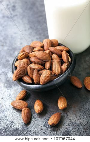 Almonds with almond milk, on dark slate background.