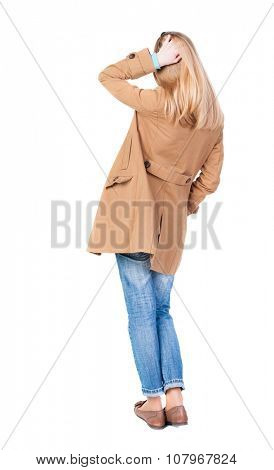back view of standing young beautiful  blonde woman in brown cloak.