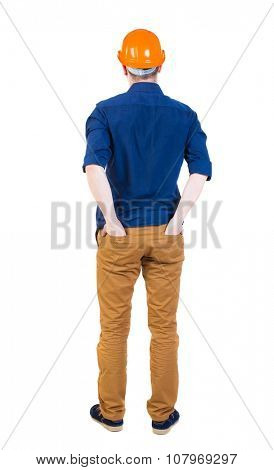 Backview of an engineer in construction helmet stands. Standing young guy. Rear view people collection.  backside view of person.  Isolated over white background. ahead.