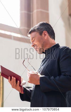 Catholic priest reading bible in church