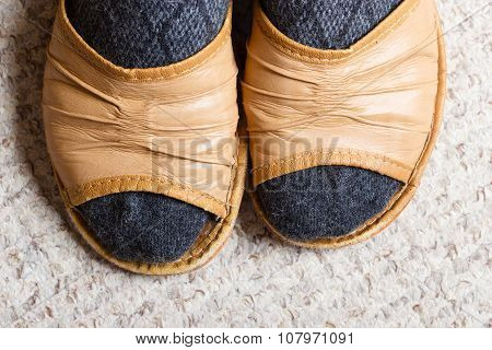 Woman Feet With Socks In Slippers At Home