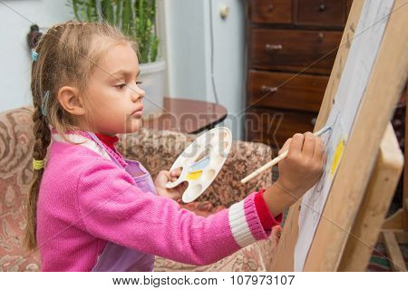 The Girl Draws A Picture Paints On An Easel In The Studio Of The Artist