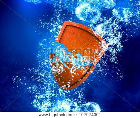 Shield sinking and dissolving in clear blue water