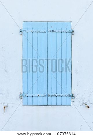 Closed blue wooden shutters, white wall