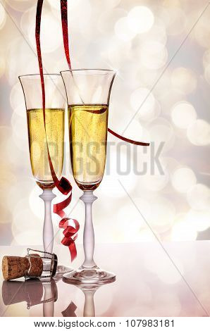 Two Glasses Of Sparkling White Wine And Cork On Table