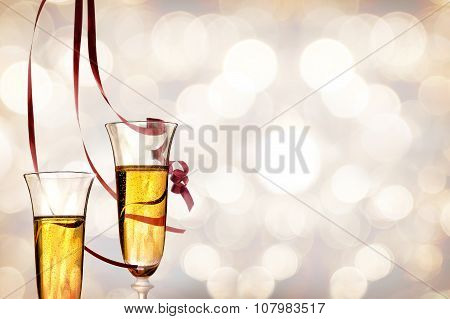 Two Glasses Of Sparkling White Wine And Ribbons Hanging