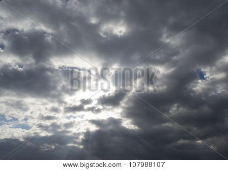 The Sun's Rays Through The Thick Clouds On Blue Sky