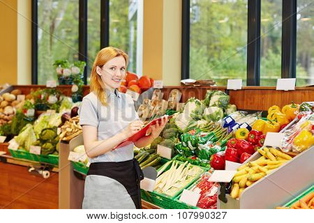 Young smiling woman making training for retail salesperson in a supermarket