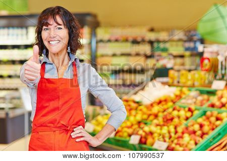 Happy elderly saleswoman holding her thumbs up in a supermarket