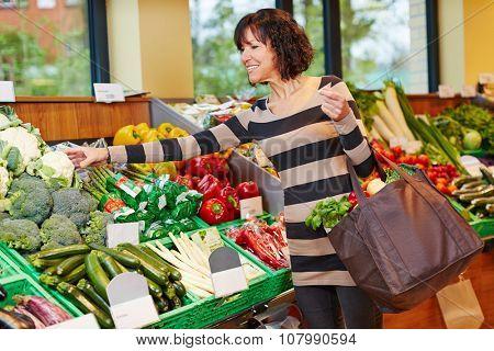 Elderly woman buying fresh vegetables in organic food store