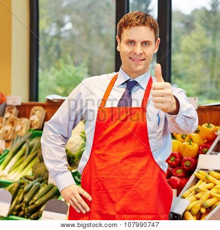 Smiling happy supermarket employee holding his thumbs up