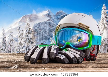 Colorful ski glasses, gloves and helmet on wooden table. Winter ski theme.